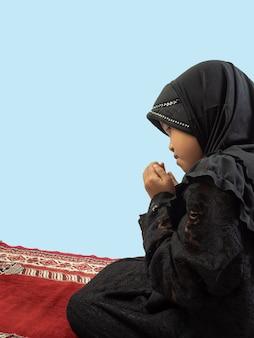 Menina muçulmana em um vestido orando