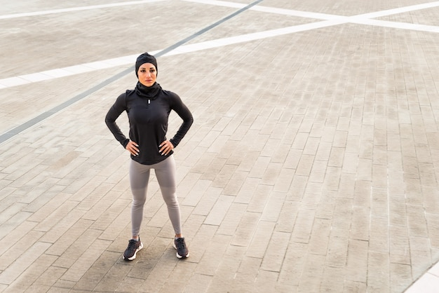 Menina muçulmana esportiva com exercícios físicos ao ar livre
