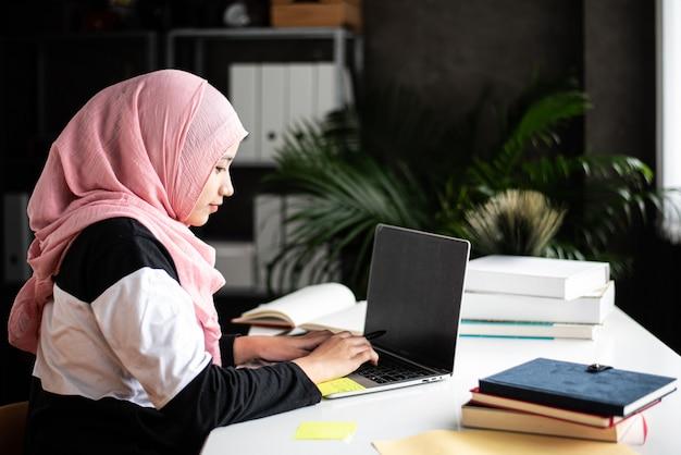 Menina muçulmana fazendo trabalho em casa