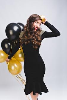 Menina muito charmosa com cabelo castanho comprido e encaracolado comemorando aniversário em branco