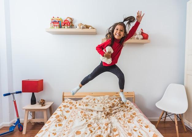 Menina muito feliz no suéter vermelho de t-shirt de gola longa pulando na cama.