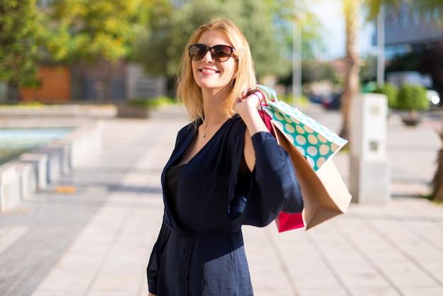 Menina muito jovem adolescente segurando um monte de sacos de compras