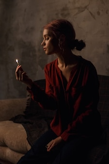 Menina muito pensativa em uma camisa vermelha com um decote profundo com cabelo recolhido