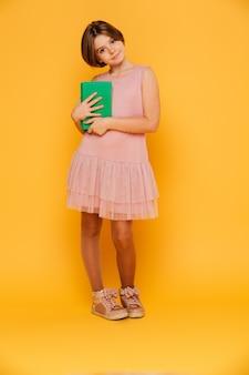 Menina muito pensativa olhando a câmera e segurando o livro verde isolado