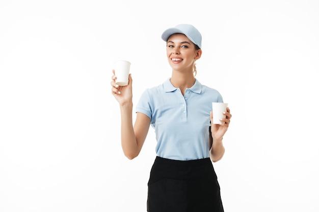 Menina muito sorridente com camiseta polo azul e boné segurando copos descartáveis nas mãos enquanto sonhadora