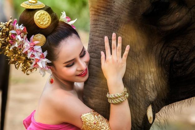 Menina muito tailandesa no vestido tradicional tailandesa com elefante
