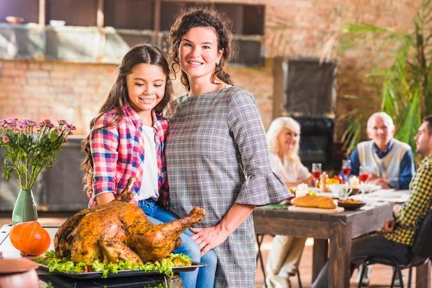 Menina, mulher, abraçar, perto, assado, galinha