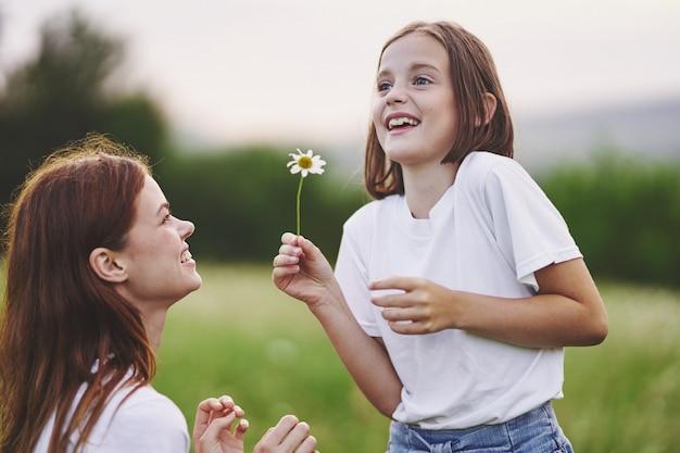Menina mulher e criança em um campo com flores colhendo flores silvestres