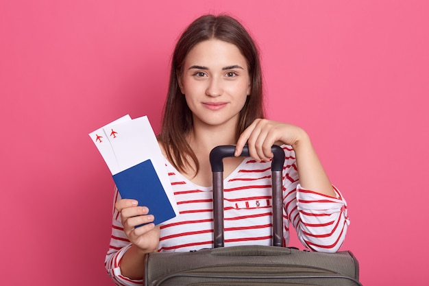 Menina mulher feliz com mala, bilhete e passaporte posando isolado sobre fundo rosa