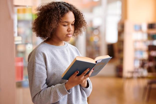 Menina multicultural de cabelos ondulados e moletom cinza lendo um livro de contos na biblioteca da faculdade
