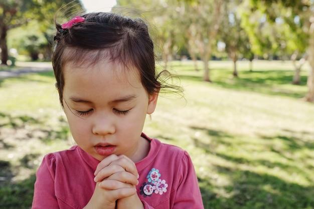 Menina multiétnica rezando no parque, criança, criança rezar conceito