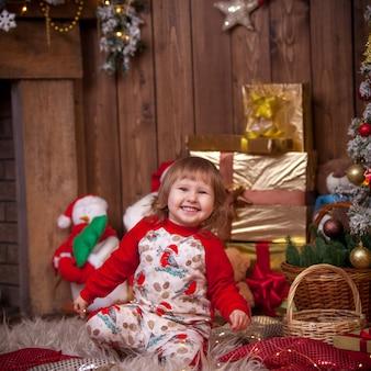 Menina na árvore de natal com presentes