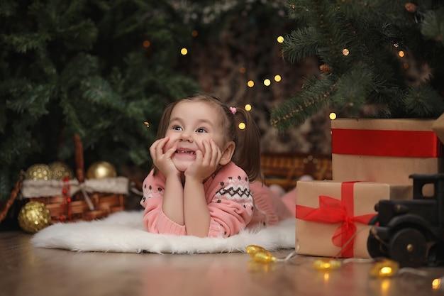 Menina na atmosfera de natal de ano novo. a menina está feliz com o natal e os presentes. uma criança na árvore de ano novo com presentes.