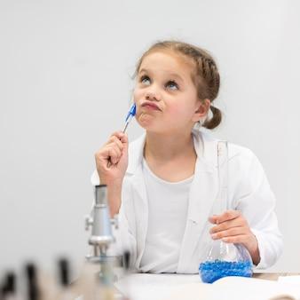 Menina na aula de ciências fazendo pesquisas