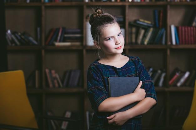 Menina na biblioteca com livros de forma estrita está envolvida na educação e no treinamento