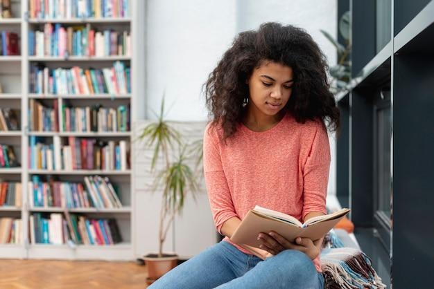 Menina na biblioteca, sentada no chão durante a leitura