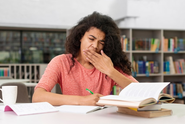 Menina na biblioteca, sentindo-se sonolento