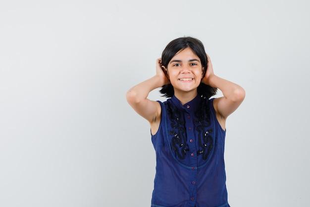 Menina na blusa azul de mãos dadas no cabelo e olhando bonita, vista frontal.