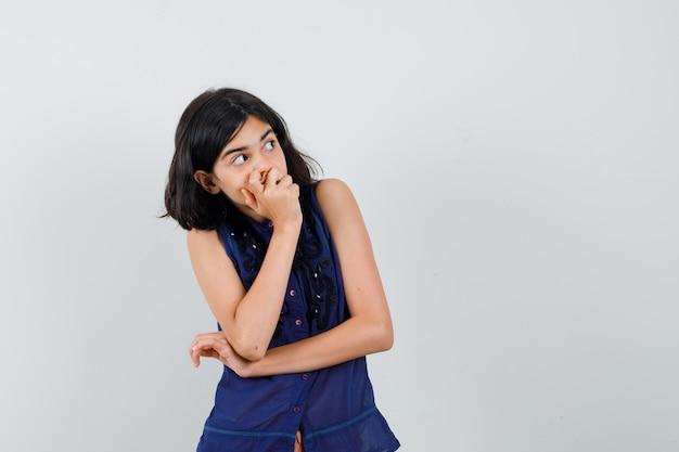 Menina na blusa azul, segurando a mão na boca, olhando para cima e olhando curiosa, vista frontal.
