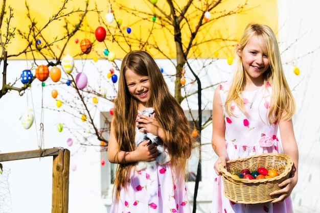 Menina na caça aos ovos de páscoa com a vida coelhinho da páscoa