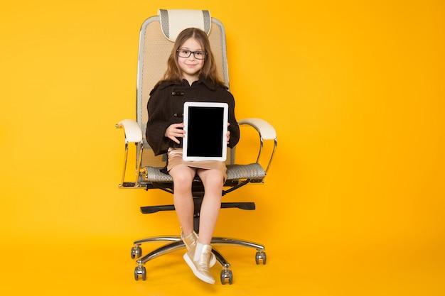 Menina na cadeira com computador tablet