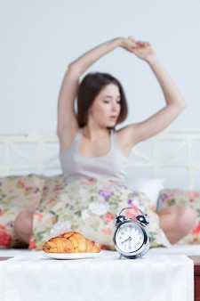 Menina na cama com serviço de relógio