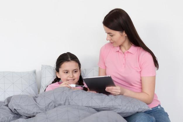 Menina na cama com tablet Foto gratuita