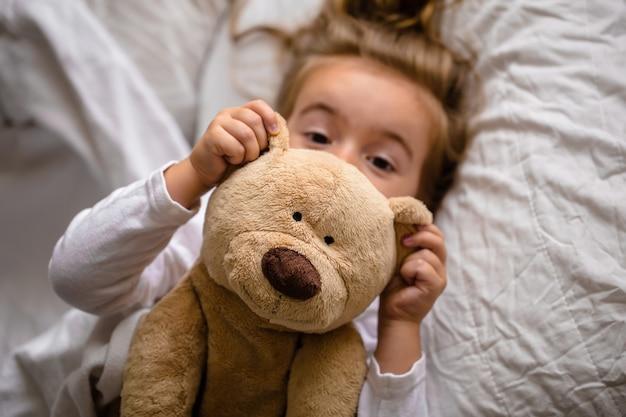 Menina na cama com um brinquedo macio as emoções de uma criança
