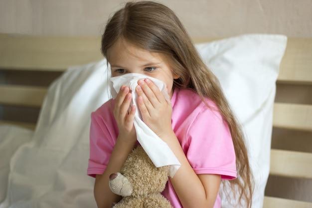 Menina na cama espirrando ou usando uma toalha para limpar o ranho do nariz e abraça seu ursinho de pelúcia