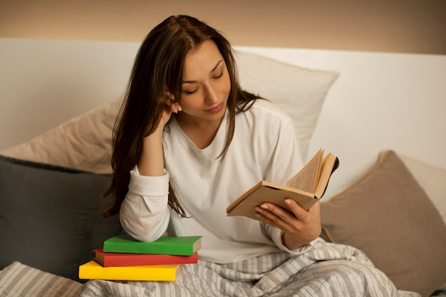 Menina na cama lê um livro antes de dormir
