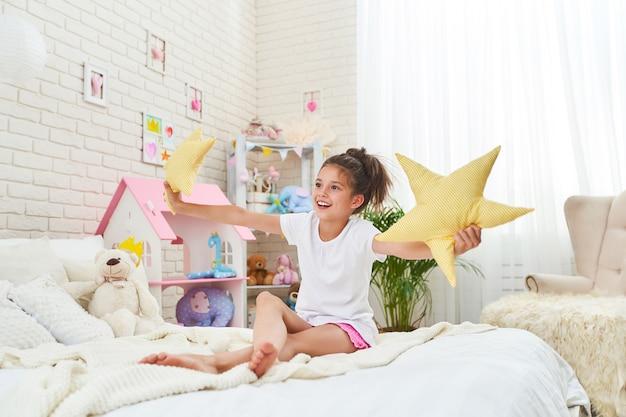 Menina na cama no quarto infantil brilhante da manhã se estende alegremente