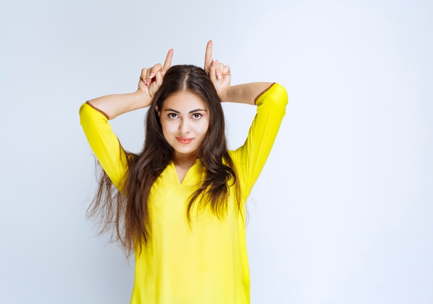 Menina na camisa amarela fazendo orelhas de lobo.