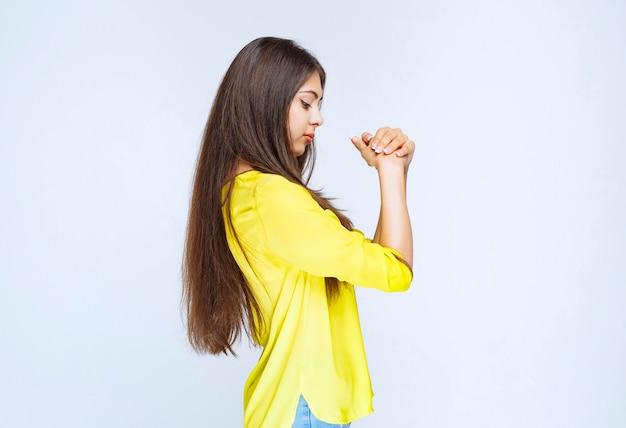 Menina na camisa amarela, unindo as mãos e sonhando.