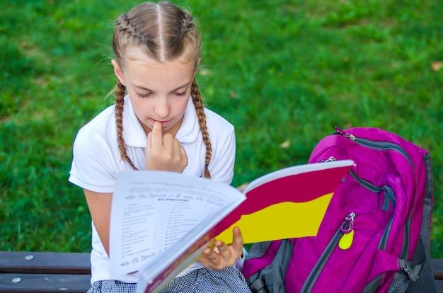 Menina na camisa branca sentado e lendo um livro. criança pensativa no pátio da escola benc