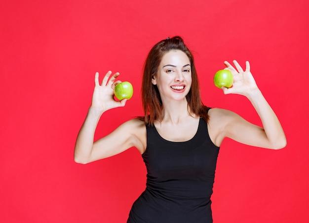 Menina na camiseta preta segurando maçãs verdes.