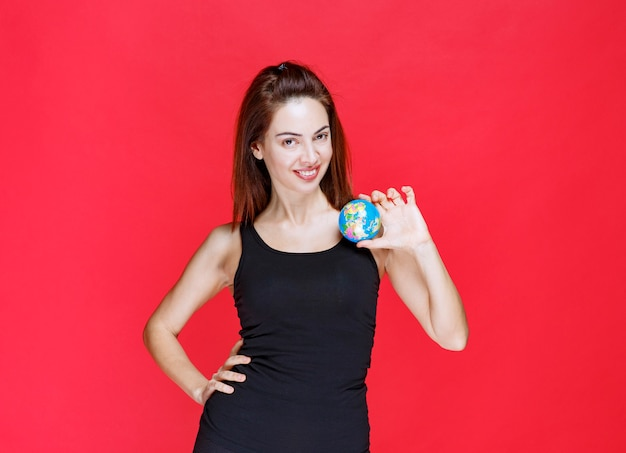 Menina na camiseta preta segurando um mini globo do mundo.