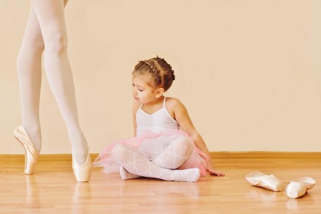 Menina na escola de ballet, olhando nas pernas de bailarina