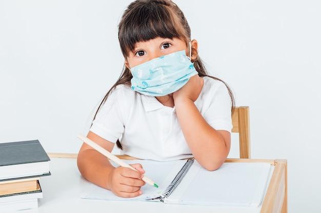 Menina na escola usando máscara cirúrgica escrevendo