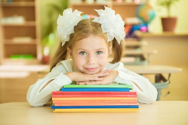 Menina na farda da escola que senta-se na sala de aula com livros. aluno em sala de aula na escola