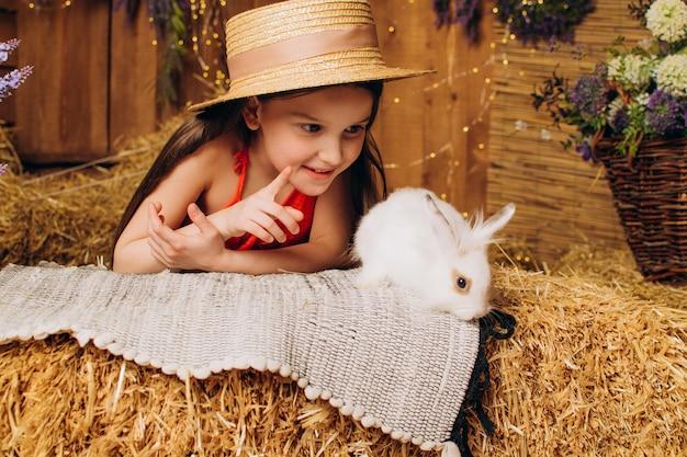 Menina na fazenda sentada com um coelho conceito do feriado da páscoa