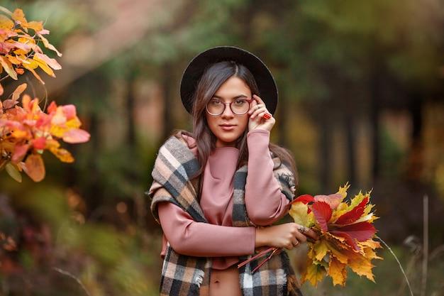 Menina na floresta de outono com um buquê de folhas de outono