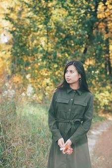 Menina na floresta de outono no pôr do sol.