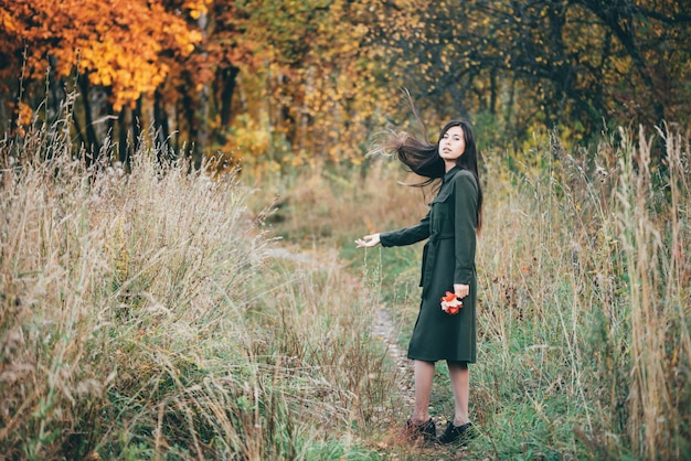 Menina na floresta de outono.