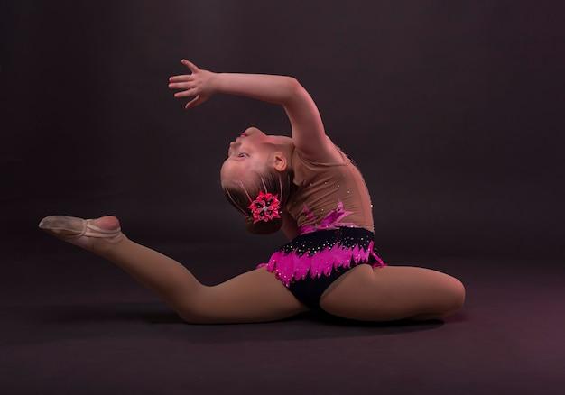 Menina na ginasta fantasiada, sentada em posição no estúdio, tentando fazer o círculo com a perna e o braço.