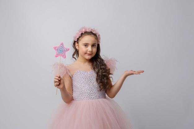 Menina na imagem de uma fada com uma varinha mágica em um fundo branco