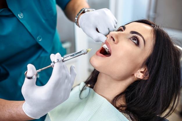 Menina na inspeção de um dentista em odontologia