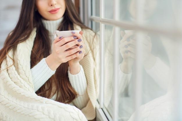 Menina na janela com uma xícara de café no inverno.