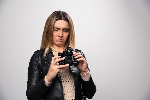 Menina na jaqueta de couro, verificando o histórico das fotos na câmera e parece insatisfeita.