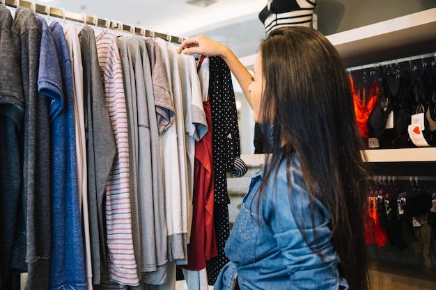 Menina na loja que está explorando roupas