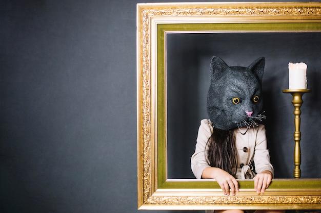 Menina na máscara atrás do quadro